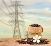 Coffee beans in burlap sack on wooden table with blur background Stock Photo