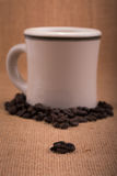 Coffee beans on burlap, with a white coffee cup on background Stock Photography