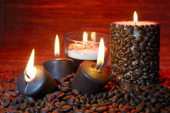 Coffee beans and burning candles Stock Photography