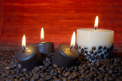 Coffee beans and burning candles Stock Photo