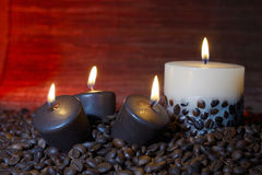 Coffee beans and burning candles Royalty Free Stock Photo