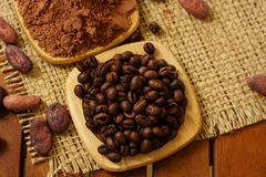 Coffee beans, cacao powder, on wooden plates on burlap stock photography