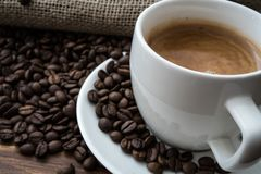 Coffee beans, caffee. Coffee beans with cup of coffee on wooden table, brown, warm, shallow, detail Royalty Free Stock Images