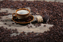 Coffee beans and cakes. Coffee beans in a coffee cup and some cake, one biscuit Royalty Free Stock Image