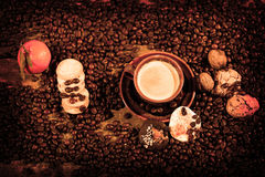 Coffee beans and cakes. Coffee beans in a coffee cup and some cake, one biscuit Royalty Free Stock Photography