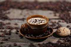 Coffee beans and cakes. Coffee beans in a coffee cup and some cake, one macaron cake Royalty Free Stock Image