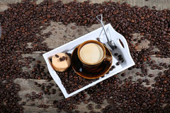 Coffee beans and cakes. Coffee beans in a coffee cup and some cake, one macaron cake Royalty Free Stock Photo