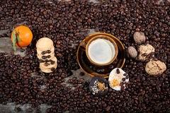 Coffee beans and cakes. Coffee beans in a coffee cup and some cake, one macaron cake Royalty Free Stock Photography