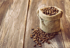 Coffee beans in the canvas sack. Vintage style photo of the coffee beans in the canvas sack at the wooden background Stock Photo