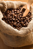 Coffee beans in canvas sack with wooden scoop Stock Image