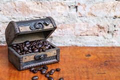 The coffee beans in the chest. On the wood table Royalty Free Stock Image