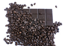 Coffee beans and chocolate. Coffee beans spilling onto dark chocolate royalty free stock photo