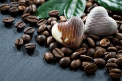Coffee beans and chocolate candies on a dark background, closeup Stock Photo