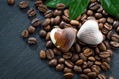Coffee beans and chocolate candies in heart shape on dark Royalty Free Stock Image