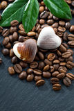 Coffee beans and chocolate candies in a heart shape on dark Royalty Free Stock Image
