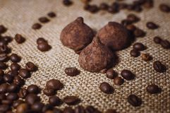 Coffee beans and chocolate candies on sackcloth close up. Coffee and sweets background royalty free stock photo