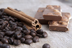 Coffee beans, chocolate and cinnamon on wooden table. Close up photo Stock Image