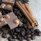 Coffee beans, chocolate and cinnamon on wooden table. Close up photo Stock Photos