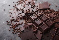 Coffee beans with chocolate dark chocolate. Broken slices of chocolate. Chocolate bar pieces. Stock Images