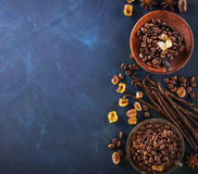 Coffee beans, chocolate drops, vanilla pods, cinnamon sticks, anise stars and brown sugar in a vintage silver cups on. A dark textural wooden background Royalty Free Stock Image