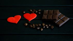 Coffee beans, chocolate and red hearts lie on a black wooden background. Still life for lovers royalty free stock photo