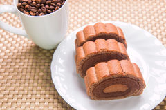 Coffee beans and Chocolate roll cake. On pattern textured wall stock image