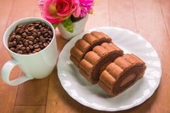 Coffee beans and Chocolate roll cake. On wooden floor stock image