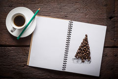 Coffee beans christmass tree. Notepad with christmass tree made of coffee beans, cup of espresso, wooden desk Royalty Free Stock Image