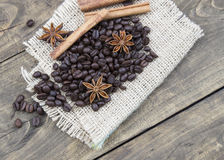 Coffee beans and cinamons on the wooden table Royalty Free Stock Photos