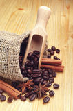 Coffee beans, cinnamon and anise. With spoon on wooden background stock photo