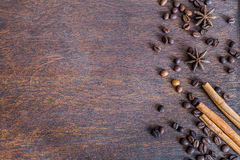 Coffee beans, cinnamon and anise stars on dark wooden backround Royalty Free Stock Images