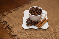 Coffee beans cinnamon cookie white cup and saucer Royalty Free Stock Photos