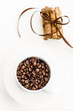Coffee beans and cinnamon. Cup with coffee beans and cinnamon sticks tied with brown ribbon Stock Images