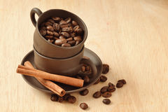 Coffee beans and cinnamon. Cups of coffee with coffee beans and cinnamon sticks Stock Image