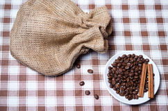 Coffee beans with cinnamon near sack on the tablecloth. Close Stock Photos