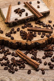 Coffee beans and cinnamon on rustic surface Stock Photos