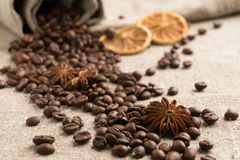 Coffee beans, cinnamon, star anise, orange dry on sackcloth. Coffee beans in a clay cup, next to nuts and dried fruits Royalty Free Stock Images