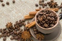 Coffee beans, cinnamon, star anise on sackcloth. Coffee beans in a clay cup, cinnamon and star anise close Royalty Free Stock Photos
