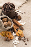 Coffee beans, cinnamon, star anise, walnuts, nutmeg, dried fruit. Coffee beans in a clay cup, next to nuts and dried fruits Stock Photos