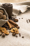 Coffee beans, cinnamon, star anise, walnuts, nutmeg, dried fruit. Coffee beans in a clay cup, next to nuts and dried fruits Royalty Free Stock Images
