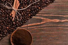 Coffee beans, cinnamon sticks and ground coffee on rustic wooden Royalty Free Stock Photography