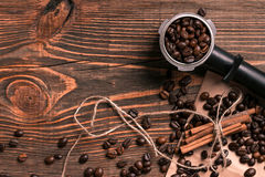 Coffee beans and cinnamon sticks on rustic wooden table, view fr Royalty Free Stock Photo