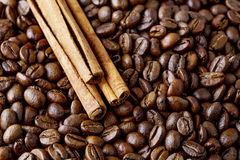 Coffee beans and cinnamon sticks. Spilling coffee beans and cinnamon sticks Stock Photos