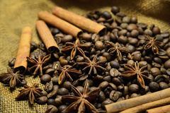 Coffee beans, cinnamon sticks and star anise. Coffee beans, cinnamon sticks, star anise on the background of old sacking, space for text Royalty Free Stock Image
