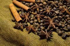 Coffee beans, cinnamon sticks and star anise. Coffee beans, cinnamon sticks, star anise on the background of old sacking, space for text Stock Photos