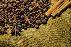 Coffee beans, cinnamon sticks and star anise. Coffee beans, cinnamon sticks, star anise on the background of old sacking, space for text Stock Photo