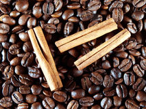 Coffee beans with cinnamon sticks on white Royalty Free Stock Photography