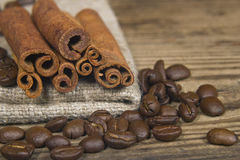 Coffee beans and cinnamon. Sticks on wooden background Royalty Free Stock Photography
