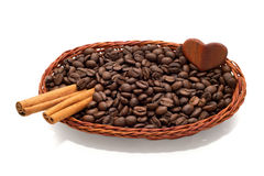 Coffee beans and cinnamon in a wicker basket with sweet little heart Stock Photography