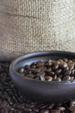 Coffee Beans in a Clay Pot V. Coffee beans in a small clay pot. Image has a background of jute fibers royalty free stock image